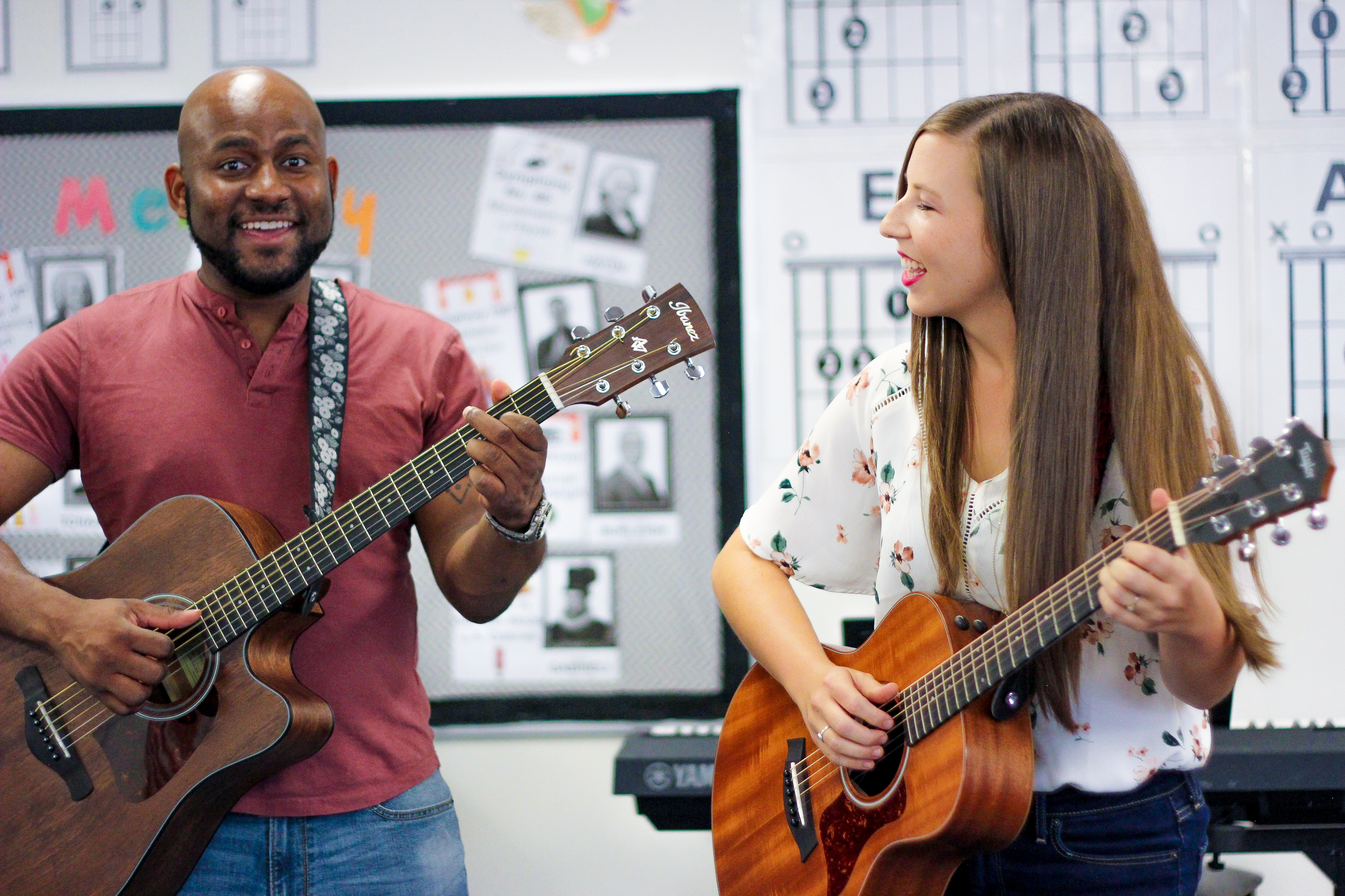 A male and female musician both playing guitars and both singing.