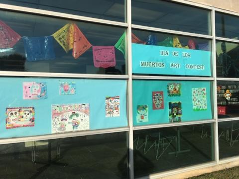 Photo of 10 student artworks on blue backing, surrounded by Dia de los Muertos decorations