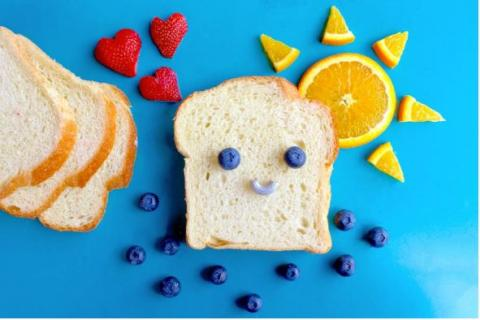 Bread and fruit arranged so a slice of bread has a smiley face
